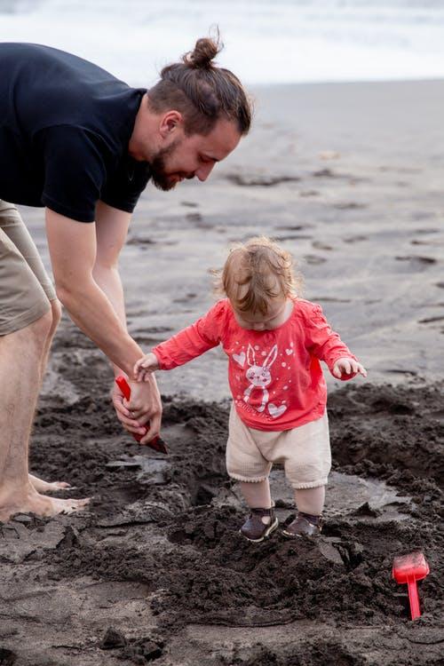 deniz kenarında oynayan çocuk ve babası